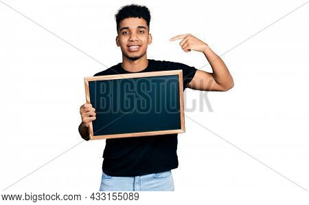 Young african american man holding blackboard pointing finger to one self smiling happy and proud