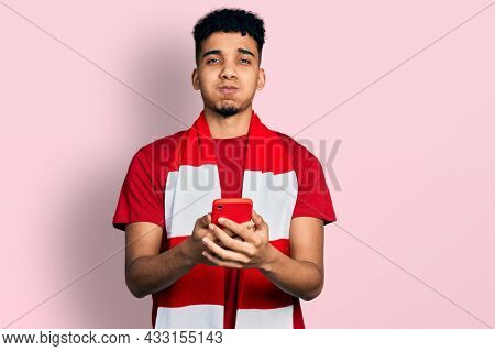 Young african american man football hooligan cheering game holding smartphone puffing cheeks with funny face. mouth inflated with air, catching air.