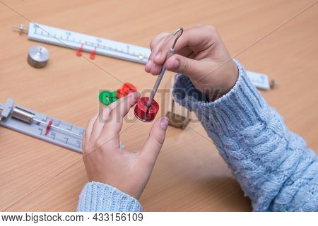 Close-up Of Hands Holding Physical Model. A Schoolboy Performs A Task At The Workplace. The Concept