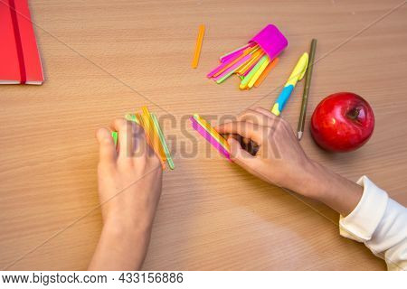 A Student At A Desk Studies Math Counting With Sticks. A Schoolboy Performs A Task At The Workplace.