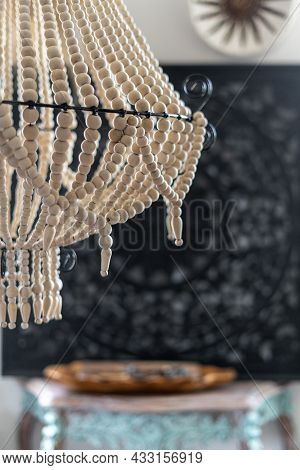 Close Up View Of White Wooden Chandelier In Boho Chic Style Hanging In Living Room With Blurred Back