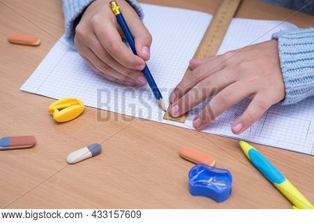 A Student In A Notebook Draws A Geometric Figure With A Pencil. A Schoolboy Performs A Task At The W