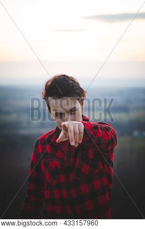 Portrait Of A Twenty-three Year Old Man In A Black And Red Checked Shirt Having Fun Watching The Sun