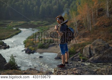 A Hippie Guy In Sunglasses Stands With A Backpack And A Ukulel On Top Of A Mountain Overlooking The