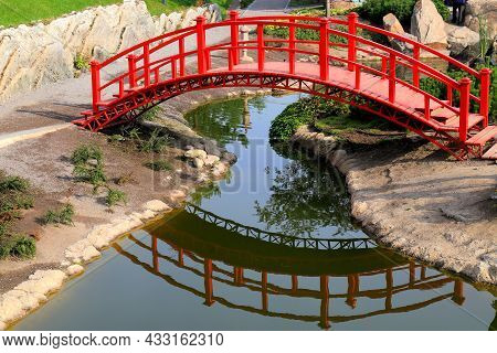 Old Red Wooden Bridge Across A Small River In A Green Park. Vintage Japanese Style Bridge Is Reflect