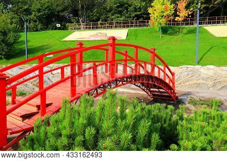 Old Red Wooden Bridge Across A Small River In A Green Park. Vintage Japanese Style Bridge Above The