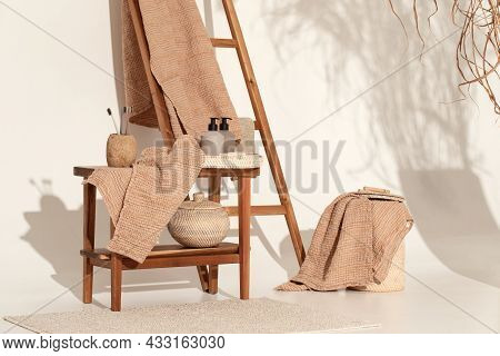 Natural Waffle Linen Towels In Earth Tones On Wood Bench And Towel Ladder With Bamboo Toothbrushes,
