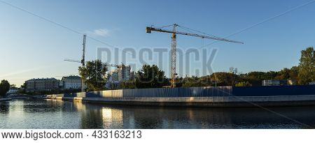 Construction Site In The City Centre With A Couple Of Tall Yellow Cranes For Lifting Heavy Construct