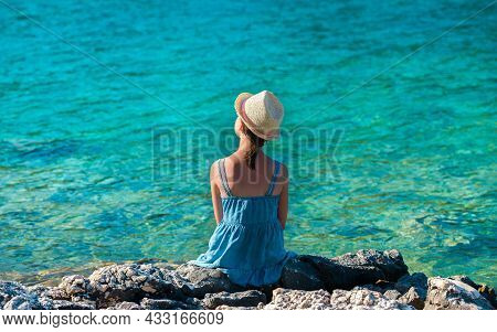 Little Girl In A Straw Hat And A Blue Summer Dress Sitting On A Rocky Sea Shore - A Shot From Behind