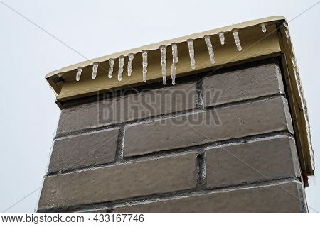 Brick Pillar Covered With Ice And Icicles After Freezing Rain