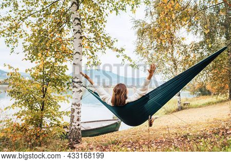 The Young Woman Cheerfully Rose Arms Up While She Swinging In A Hammock Between The Birch Trees On T