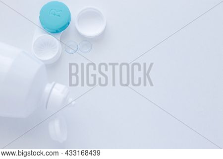 A Container For Lenses And Two Contact Lenses Lie On The Side On A White Background With Space For T
