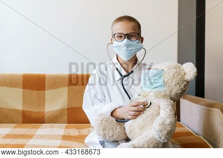 View Of Child Playing Doctor Or Nurse With Teddy Bear In Sunlight At Home. Happy Boy Listens To A St