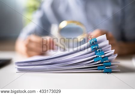 Auditor Doing Tax Fraud Investigation Using Magnifying Glass