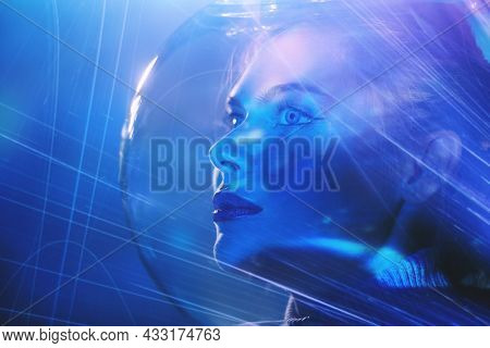 Beautiful tender girl with blue eyes in a glass spacesuit looks into the distance surrounded by cosmic light. Space concept. Copy space.