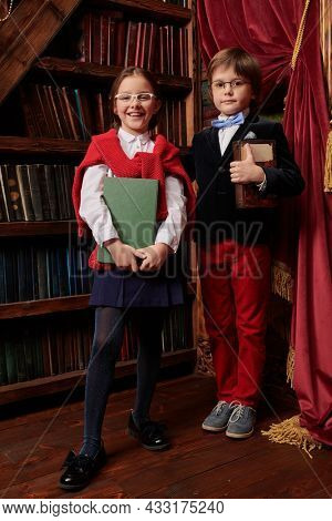 Pair of schoolchildren posing in a splended vintage interior by a bookcase with books in their hands wearing stylish, fashionable school clothes. Kid's school fashion. Full-length portrait.