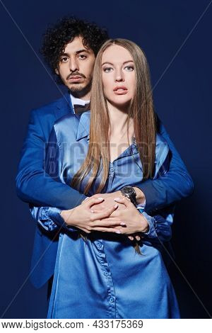 A pair of young handsome man and a beautiful woman in elegant evening wear on a dark blue background. Beauty, fashion portrait. Love and relations.