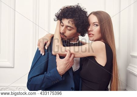 Love and passion. Beautiful young woman hugs tenderly her beloved man. Beautiful couple in love wearing evening clothes. Fashion shot.