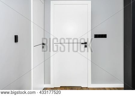 A White Door With A Ventilation Undercut With A Matte Black Handle And A Black Line In The Middle In