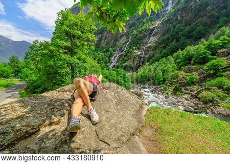 Peaceful Woman Resting At The Old Roman Stone Bridge Steinbrucke Over The Bavona River. The Waterfal