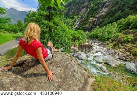Woman Relaxing Sitting At The Old Roman Stone Bridge Steinbrucke Over The Bavona River. Looking At T