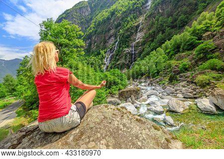 Peaceful Woman Doing Yoga Meditation In Lotus Pose At Edge Of The Old Roman Stone Bridge Steinbrucke