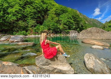 Woman Relaxes On The Rocks Of The Verzasca River. Verzasca Valley By Lavertezzo Town. Famous Landmar