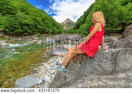 Woman Sitting On The Rocks Of The Verzasca River. Verzasca Valley By Lavertezzo Town. Famous Landmar