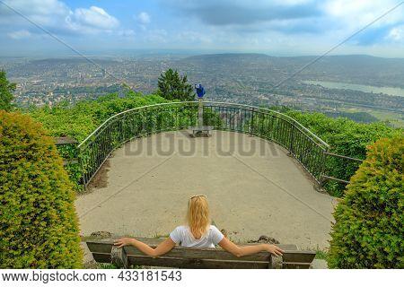 Woman Sitting On Uetliberg Mountain Lookout. Zurich Skyline On A Swiss On Uetliberg Mountain In The