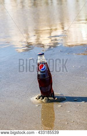 Old Orchard Beach, USA - 3rd Sept 2014: Illustrative editorial image of a bottle of Pepsi being kept cold in the sea. Pepsi is a popular carbonated soft drink produced by PepsiCo since 1893