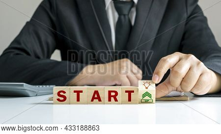 Businessman Flipping Wooden Cube Blocks With Words Startup By Hand, Business Start-up Ideas And Inno