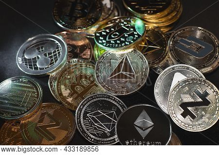 A Lot Of Cryptocurrency Coins Lie On A Dark Surface Background. View Of Cryptocurrency Tokens, Bitco