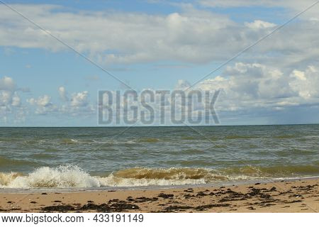 The Baltic Sea In August. Sand, Seaweed On The Shore, Waves, Beautiful Clouds And The Sun. High Qual