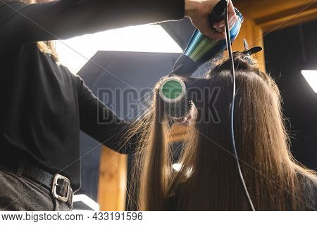 Master Woman Hairdresser Dries The Girls Hair With A Hairdryer And Combs After Washing In The Beauty