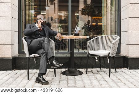 Portrait Of A Black African American Businessman In A Suit Sitting In A City Cafe Outdoors And Talki