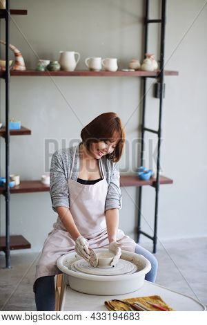 Pretty Positive Young Asian Woman Using Rigid Wooden Rib For Achieving Better Form Of Dish On Potter