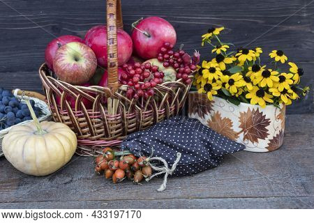 On A Dark Background, A Basket With Apples And Viburnum, A Bouquet Of Yellow Flowers, A Bag Of Rose