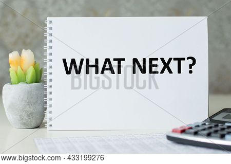 What's Next Words Are Written On A White Notebook That Stands On The Table Next To The Calculator.