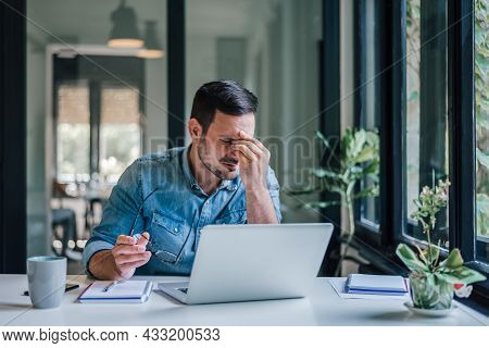 Businessman Office Working Holding Sore Head Pain From Desk Working And Sitting All Day Using Laptop