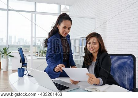 Smiling Businesswomen Discussing Document With Order Of Company Ceo