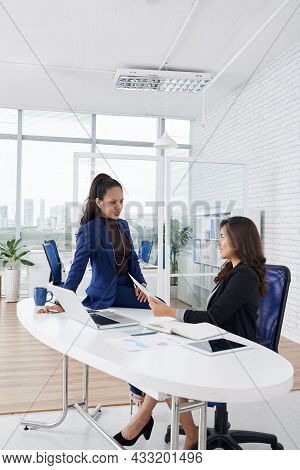 Elegant Female Entrepreneurs Discussing Report With Annual Statistics Before Meeting With Company Ce