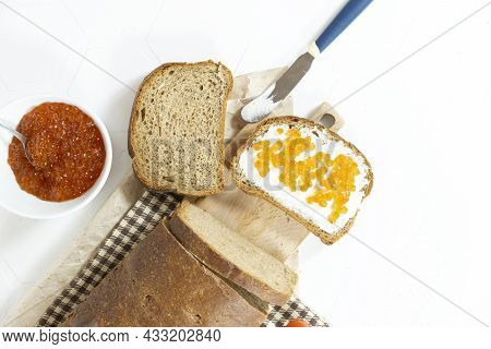 Red Caviar In Bowl And Sandwiches On Wooden Cutting Board On White Background Close-up