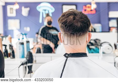 Back Of A Caucasian Man Sitting In A Hairdressers Salon With A Dressing Gown And Mask