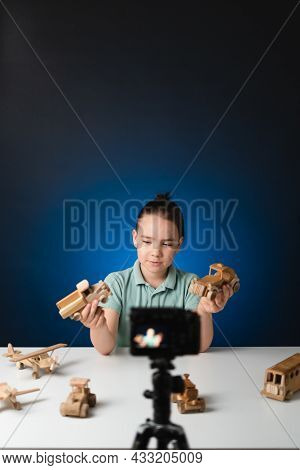 Kid Blogger Filming Video On Camera Indoors With Blue Light In Background. Online Reviewing. Promoti