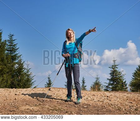 Summer Hike In The Mountains. Lonely Woman With Backpack And Trekking Poles Stopping To Rest On Dirt