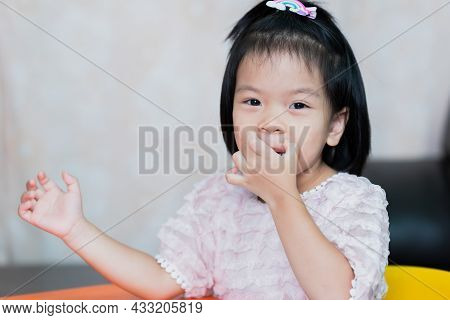 A Cute Little Girl Is Scratching Her Lips From Itching. Children Secretly Smile.