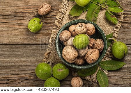 Ripe Brown And Unripe Green Walnuts In A Bowl