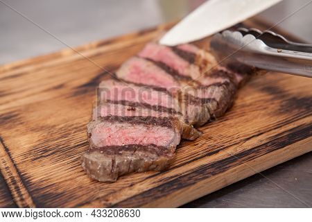 Chef Cutting Medium Rare Grilled Beef Steak On Wooden Cutting Board