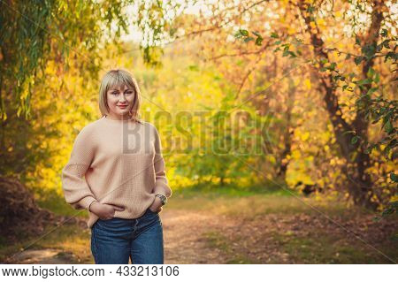A Blonde Woman With A Short Haircut Walks Through The Forest In A Knitted Sweater. Outdoor Hiking In