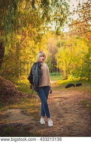 A Blonde Woman With A Short Haircut Walks Through The Forest In A Knitted Sweater And Two Big Black